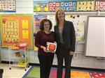 Cindy Evans accepts the March 16 Game Ball from Dr. Meadows